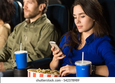 Have to reply this. Attractive woman using her phone at the movie theatre beauty entertainment busy communication gadget technology online connectivity weekend texting concept