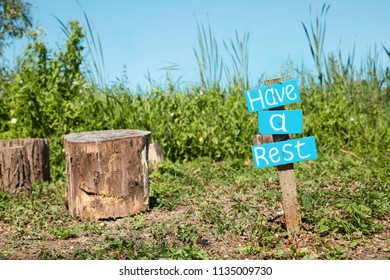 """Have a rest"" wooden blue Sigh surrounded by natural environment and stump near by at nature reserve in UK, Europe"