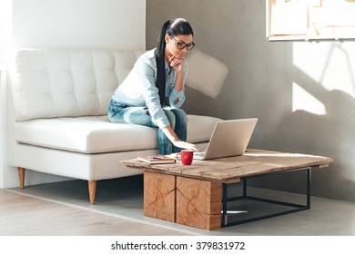 Have some work to do. Beautiful young woman in glasses working on laptop while sitting on the couch in office