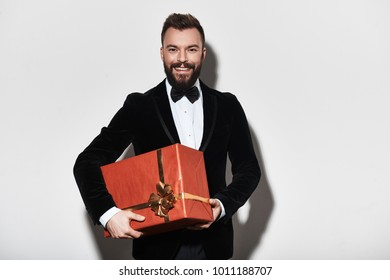 I have something for you. Handsome young man in full suit carrying a gift box and smiling while standing against grey background