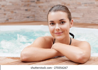 Have a splendid time. Close-up of a young beautiful woman enjoying a jacuzzi in a spa center