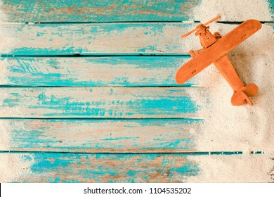 Have a vacation and travel in summer concept - top view of beach sand and toy air plane on wood plank in blue sea paint background.