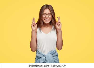 I have to win. Joyful young brunette female clenches teeth, raises fingers crossed, makes desirable wish, wears round spectacles and casual clothes, waits for good news, stands indoor over yellow wall