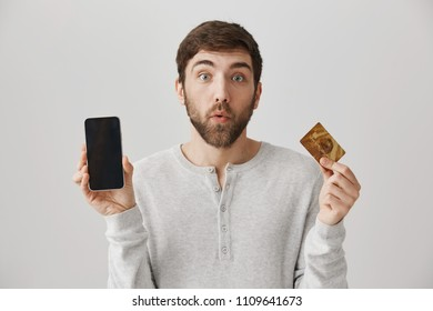 Have you heard about online shopping. Handsome curious man showing smartphone and credit card, looking impressed and intrigued while standing over gray background. Man wants to buy phone in credit