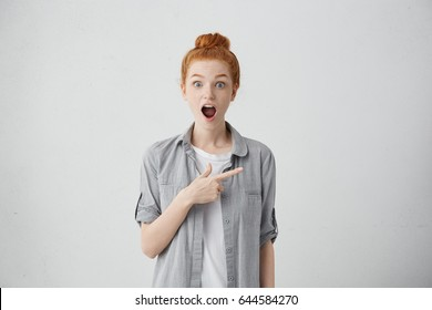 Have you seen that? Indoor shot of emotional surprised young European woman staring at camera in full disbelief with jaw dropped, pointing index finger sideways, showing something on grey wall