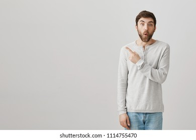 Have you seen what happened there. Portrait of interested excited handsome man with beard pointing left or behind while expressing surprise and shock after hearing intriguing rumor