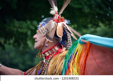 HAVERHILL, MASSACHUSETTS/USA - SEPTEMBER 9, 2018: A Native American man from the Pokanoket Wampanoag tribe wearing traditional buckskin clothes and hawk feather headdress at a local pow-wow.
