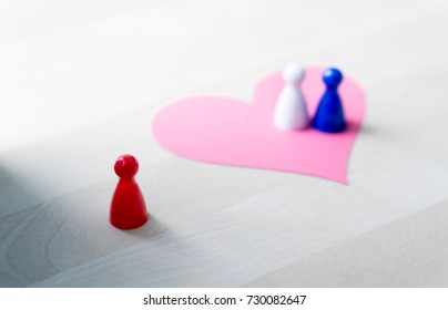 Having affair, infidelity or cheating concept. Love triangle or being third wheel. Board game pawns and paper heart on table.