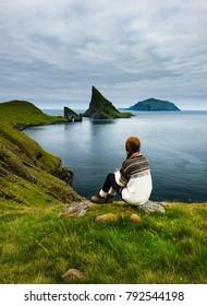 having a break on a long hike, enjoying the view of the rock formations on Vagar Island (Faroe Islands)