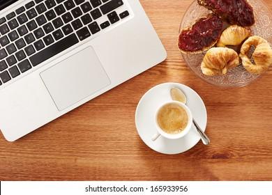 Having breakfast in front of computer on workspace