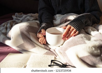 Having coffee and reading in bed on lazy sunny morning. Female hands holding steaming cup of hot cocoa reading in bed