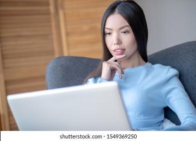 Having complicated task. Dark-eyed freelancer feeling thoughtful while having complicated task