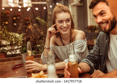 Having a drink with friends. Contended happy cheerful beautiful red-haired young female having a drink with friends at the bar
