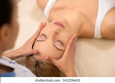 Having face massage. Young appealing blonde-haired woman closing eyes while having face massage