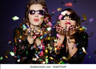 Having fun with best friend: two stylish women standing against dark background and blowing colorful confetti, waist-up group portrait