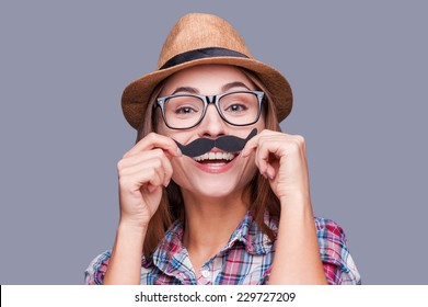 Having fun with face mustache. Cheerful young woman in funky hat holding fake mustache on her face and looking at camera while standing against grey background