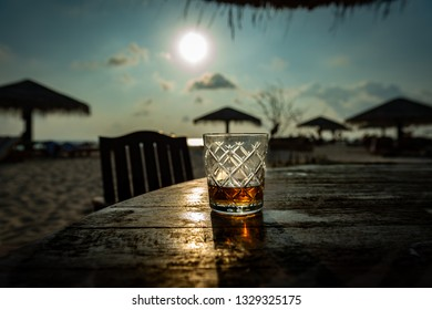 having fun with a glass whiskey on the beach