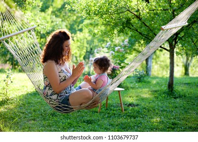 Having fun in hammock. Mother and baby girl playing in the garden. Family, relaxation, nature.