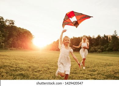 Having fun at holiday time. Mother and daughter with kite in the field. Beautiful nature.