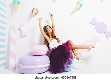 Having fun of joyful amazing model in purple tulle skirt on white heels expressing on big macaroon isolated on white background surround big sweets. Beautiful young woman in sweet dreams