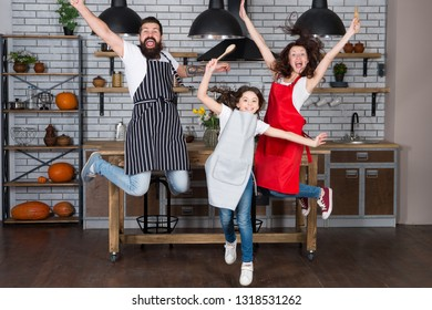 Having fun in kitchen. Family mom dad and little daughter wear aprons jump in kitchen. Family having fun cooking together. Teach kid cooking food. Weekend breakfast. Cooking with child might be fun.