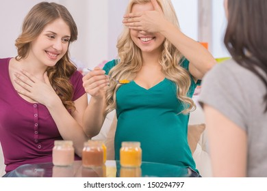 Having fun on Baby Shower. Happy young women trying baby food on baby shower