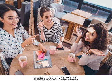 Having fun. Positive joyful woman pointing at her friend while playing together a game with her