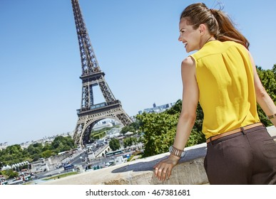 Having fun time near the world famous landmark in Paris. Seen from behind smiling young woman in bright blouse looking aside in Paris, France