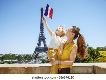 Having fun time near the world famous landmark in Paris. happy mother and child tourists rising flag in Paris, France