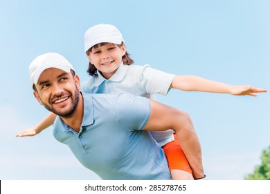 Having fun together. Cheerful young man carrying his son on shoulders while standing outdoors