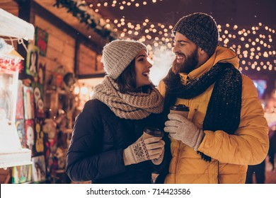 Having fun together at a christmas fairy. Young cheerful couple is having a walk with hot drinks, enjoying, dressed warm, looking at each other and laugh