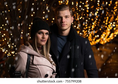 Having Fun Together at a Christmas Fairy. Young Cheerful Couple Is Having a Walk. Enjoying, Dressed Warm, Looking at Each Other and Laugh
