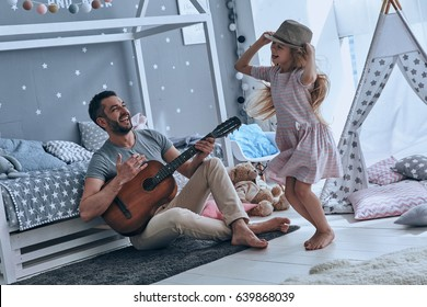 Having fun together. Young father playing guitar for his little daughter and smiling while spending free time at home