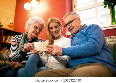 Having funny time with grandparents, family smiling together while looking old photos