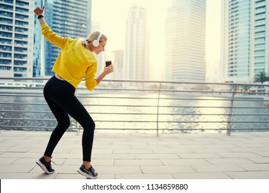 Having good mood. Enjoying the sound. Happy young woman with earphones listening music on smartphone while dancing on city embankment.