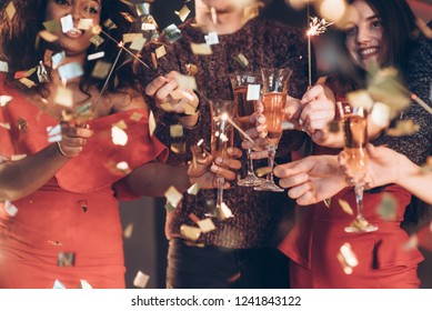 Having good mood and nice time. Multiracial friends celebrate new year and holding bengal lights and glasses with drink.