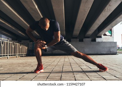 Having a good stretch. Handsome young African man in sports clothing stretching while warming up outdoors