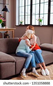 Having hug with granny. Elderly white-haired good-looking granny wearing casual clothes having a hug with attractive slim short-haired granddaughter in pink blouse on grey sofa