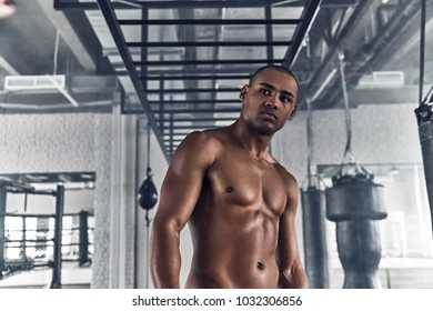 Having a little break. Shirtless young African man looking away while standing in the gym