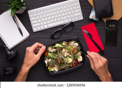 Having lunch at workplace. Businessman enjoying healthy salad at work desk, top view