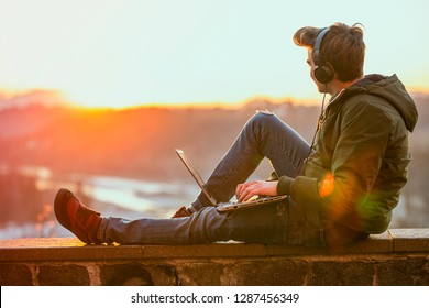 Having opportunity to work everywhere. Handsome young man working on laptop and smiling while sitting outdoors - Immagine
