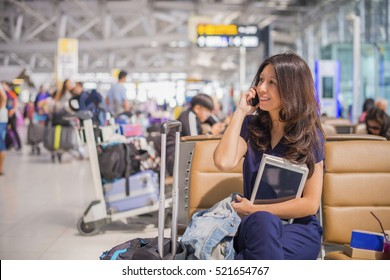 Having opportunity to work everywhere. Smilling Asian businesswoman working at airport terminal talking mobile phone and using tablet on background blur passenger. (lens blur effect)