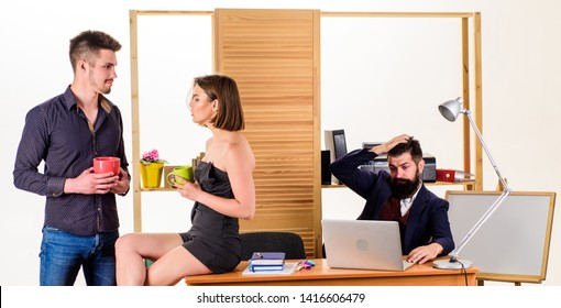 Having rest for good work. Pretty woman and handsome man having rest in office while colleague working in background. Managers drinking tea in rest hour. Young coworkers enjoying rest break at work.