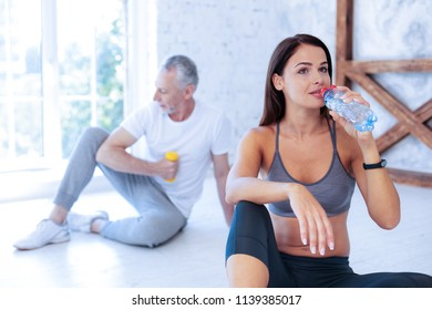Having rest. Silhouette of elderly sportsman that sitting on the background and holding yellow dumbbell while looking aside