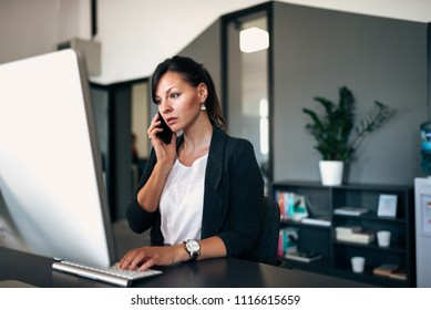 Having serious phone conversation with colleague while solving problem on the computer.
