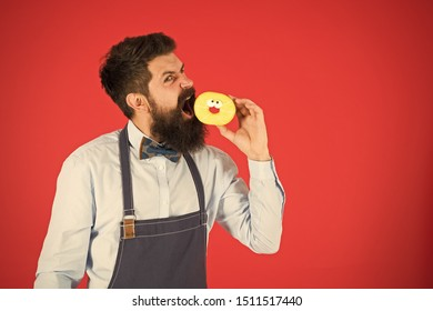 Having snacks. Diet and healthy food. Baker eat doughnut. Chef man in cafe. Calorie. Feel hunger. Bearded baker. Bearded man in apron. baker hold donut. Funny hipster. Professional baker.