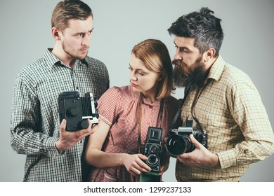 Having some problems. Group of photographers with retro cameras. Retro style woman and men hold analog photo cameras. Paparazzi or photojournalists with vintage old cameras. Photography studio.