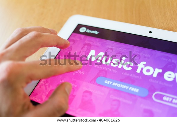 HAVIROV, CZECH REPUBLIC - APRIL 11, 2016: Man's hand use with his fingers tablet. Spotify app on the screen. Spotify is service for streaming and listening music on internet