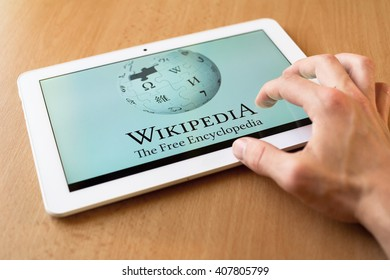 HAVIROV, CZECH REPUBLIC - APRIL 15, 2016: Man's hand use with his fingers tablet. Wikipedia app is on the screen. Wikipedia is popular free-access online encyclopedia (shallow selective focus)
