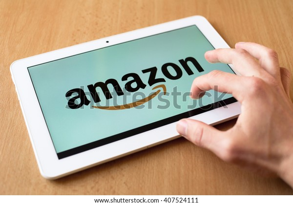 HAVIROV, CZECH REPUBLIC - APRIL 15, 2016: Man's hand use with his fingers tablet. Amazon app is on the screen. Amazon is popular retailer with various kinds of goods. (shallow selective focus)